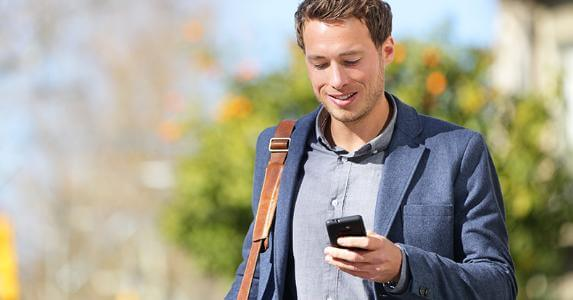 man-with-smartphone-walking-outside-shoulderbag_573x300